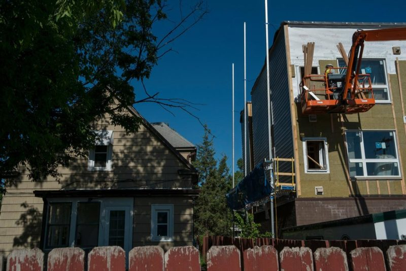 A new apartment complex being built next to a single-family home in South Minneapolis