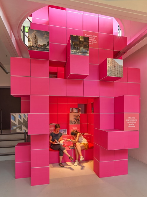 The pixel tower is constructed from hundreds of bright pink cardboard boxes