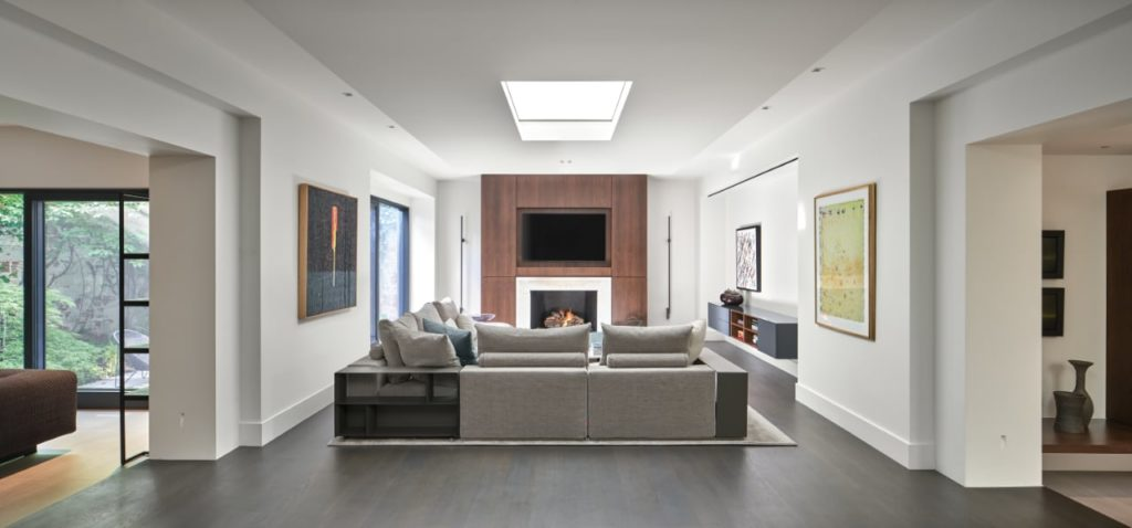 Contemporary light-filled interior that incorporates a rich material palette of wood, stone, bronze and leather