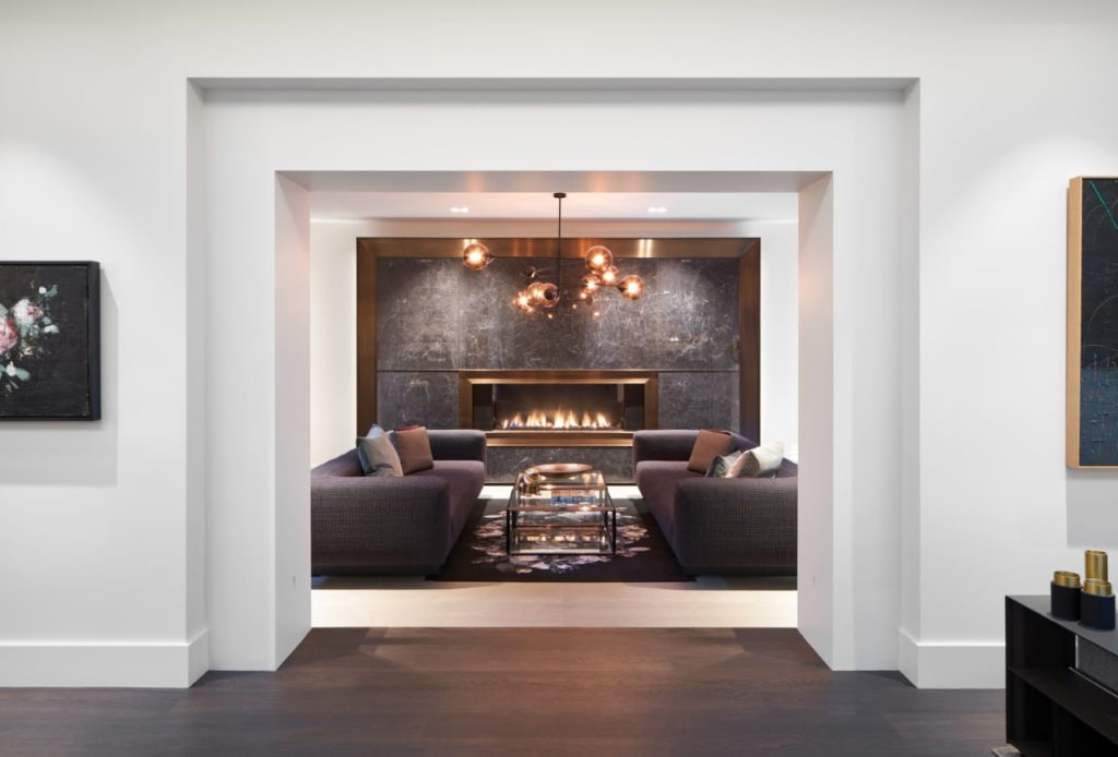 Linear gas fireplace is inset into a dramatic wall of dark veined stone trimmed in bronze.