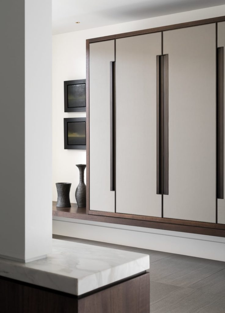 Built-in millwork, combining walnut, lacquered wood and custom closet doors of leather trimmed in bronze